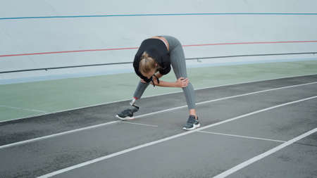 Female runner with prosthetic leg preparing for workout on sports track. Sporty woman stretching body at modern stadium. Active girl exercising on track outdoors in slow motion