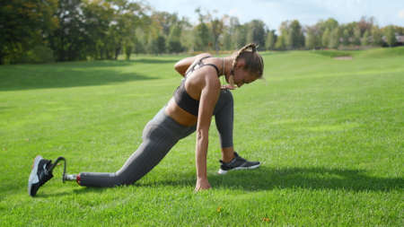 Handicapped woman stretching legs in green park. Female athlete exercising in morning. Athletic girl doing warming exercise before fitness training at summer park in slow motion