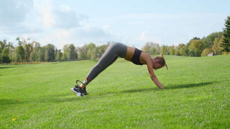 Young disabled woman stretching legs at summer park. Sporty girl practicing yoga in green field. Sportswoman warming before workout outdoors in slow motion