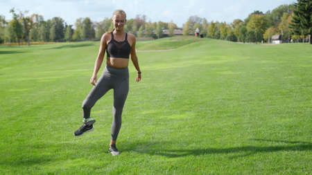 Sporty woman with prosthetic leg warming before morning workout in park. Fit girl exercising outdoors in slow motion. Disabled woman doing fitness exercise in summer park