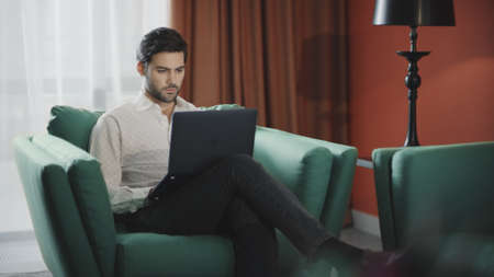 Handsome businessman working laptop computer in luxury hotel. Business man working computer at remote workplace. Remote worker typing notebook at modern apartment.