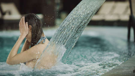 Close up of pretty girl getting spa treatment in pool. Beautiful woman having hydrotherapy in pool at luxury hotel. Attractive woman enjoying water massage indoor