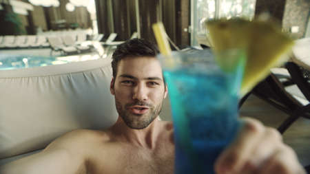 Close up of handsome man posing for camera with alcohol cocktail at hotel spa. Portrait of attractive guy call video chat online at pool. Cheerful person recording video from vacation at poolside. Banco de Imagens