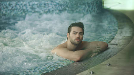 Handsome man resting in jacuzzi spa at luxury hotel. Sexy man relaxing in whirlpool bath at modern wellness center. Young guy having hydrotherapy indoor. Banco de Imagens