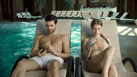 Young couple watching mobile phones near pool. Beautiful family relaxing with phones on loungers at wellness center. Romantic couple chatting on cellphones at wellness center.