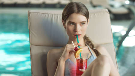 Portrait of young woman drinking cocktail poolside at luxury spa. Beautiful woman flirting in lounger indoor in slow motion. Pretty girl looking around near swimming pool with alcohol.