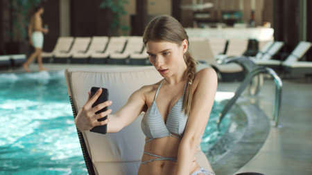 Portrait of young woman making selfie photo on lounger near swimming pool. Closeup sexy girl making v gesture on mobile phone at luxury pool. Beautiful woman posing for self portrait in slow motion.