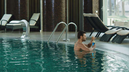 Attractive man drinking cocktail at luxury pool indoor. Sexy guy relaxing with alcohol cocktail at pool. Handsome man resting at luxury spa with alcohol. Banco de Imagens