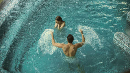 Happy couple having fun in pool at luxury spa. Lovely couple splashing together in slow motion at pool. Smiling man and woman bathing together indoor.