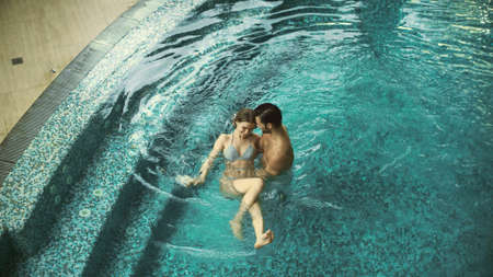 Top view of smiling couple swimming in pool at luxury spa together. Lovely man and woman resting at whirlpool indoor. Cheerful couple enjoying pool on honeymoon. Banco de Imagens - 160490202