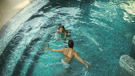 Top view of cheerful couple swimming in pool indoor. Lovely couple having fun in whirlpool bath together. Beautiful family bathing in pool at wellness hotel. Banco de Imagens