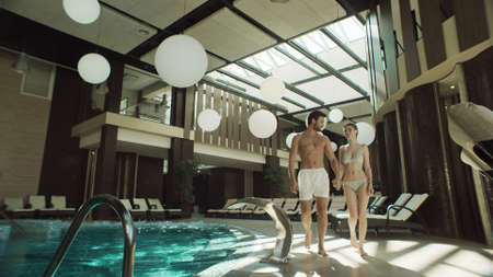 Cheerful couple walking indoor pool in swimsuits. Closeup smiling man and woman holding hands near swimming pool. Happy couple resting near poolside together.