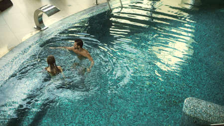 Above view of cheerful couple swimming in pool indoor. Beautiful couple relaxing in pool together. Joyful man and woman enjoying water procedures in luxury hotel. Banco de Imagens