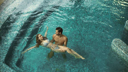 Top view of joyful couple bathing at spa resort. Happy man and woman swimming at luxury pool indoor. Cheerful couple enjoying pool at spa hotel together.