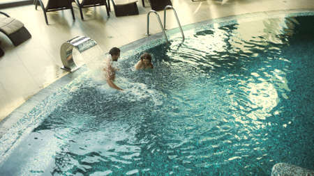 Cheerful couple enjoying hydrotherapy at wellness resort. Happy couple bathing at luxury spa together. Smiling man and woman relaxing in whirlpool bath. Young people having fun in water indoor. Banco de Imagens