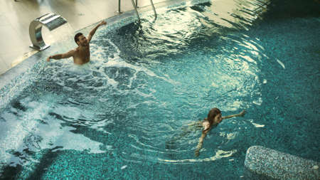 Cheerful couple enjoying hydrotherapy at wellness resort. Top view of young couple bathing at luxury spa together. Happy man and woman relaxing in whirlpool bath indoor.
