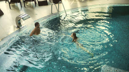 Top view of cheerful couple enjoying swimming at wellness resort. Happy couple bathing at luxury spa together in slow motion. Relaxed man and woman resting in whirlpool bath indoor. Banco de Imagens