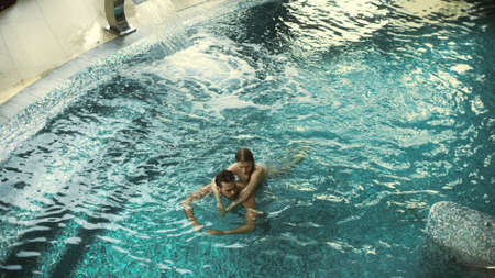 Top view of relaxed couple hugging in pool at spa resort. Happy man and woman enjoying relax in water together at wellness hotel. Young couple swimming in pool spa in slow motion.