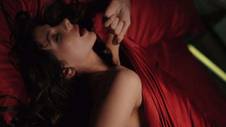 Closeup passionate girl dreaming about in red silk bed. Portrait of young woman lying under satin sheet in bed. Sensual lady with opened mouth feeling aroused in bedroom.