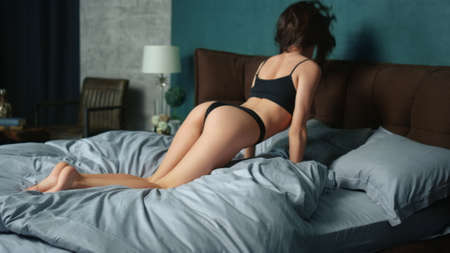 Sexy booty girl standing in doggy position on bed at home bedroom. Young woman throwing long hair in slow motion on bed at hotel room. Seductive model taking sexy poses in lingerie on bed. Stock fotó