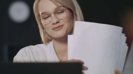 Satisfied business woman looking financial document front laptop in night office. Portrait of happy woman working late on computer in dark office. Successful business girl checking paper at workplace.