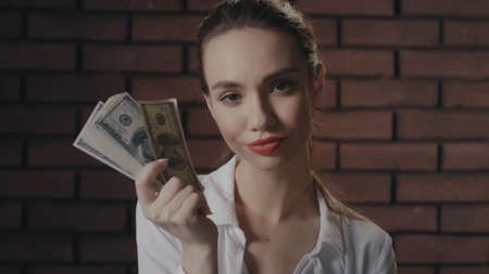Haughty woman looking to camera and showing money stack to camera in brick studio. Portrait rich and greed woman holding money cash and posing. Rich girl with dollars