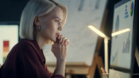 Thinking business woman working on computer in night office. Tired woman financial analyst working at late work. Overworked businesswoman analyzing business statistics at workplace. Reklamní fotografie