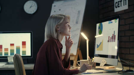 Cheerful business woman typing on computer keyboard in dark office. Smiling financial analyst preparing presentation with graphs and charts. Overworked woman sitting in front of monitor at workplace. Reklamní fotografie