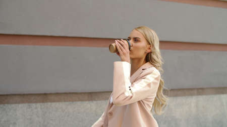 Close up female office worker going with take away coffee at street. Attractive business woman drinking coffee to go outdoors. Pretty businesswoman walking in pink suit at city street. Banco de Imagens - 158229584