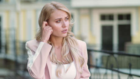 Portrait focused woman talking by wireless headset outdoor. Serious businesswoman using earphones outside. Young girl using wireless earbuds at street. Banco de Imagens - 158234321