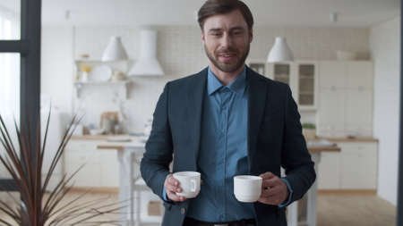 Closeup loving couple making coffee break at home. Portrait of handsome man bringing tea cups to woman at home. Happy family relaxing after work in livingroom together.