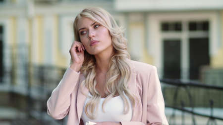 Portrait blonde woman using wireless headset for work outside. Serious businesswoman talking by earphones at street. Focused woman using headphones outdoor. Banco de Imagens