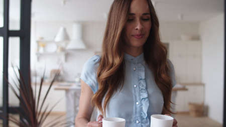 Happy woman bringing tea cups to husband at home in slow motion. Successful couple having coffee break in modern room. Closeup cheerful man discussing business with woman at remote workplace.
