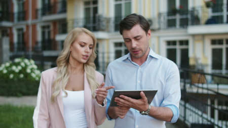 Close up young entrepreneurs using tablet computer for work online at street. Pretty business couple walking together outdoor. Stylish business partners talking about work outside.
