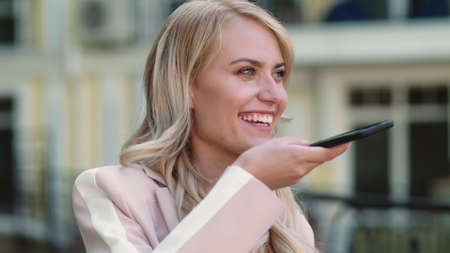 Happy woman using voice messages on smartphone at street. Portrait of smiling businesswoman recording audio message outdoor. Business woman using mobile phone in hand outdoor. Banco de Imagens - 158235213