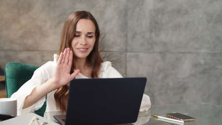 Joyful business woman making video call on laptop in modern office. Serious business lady making conference call at home. Lady making hi gesture at video chat online in slow motion.
