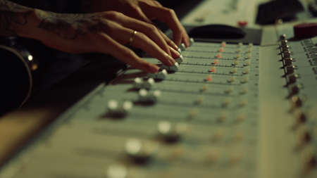 Macro man hands moving sliders on soundboard. Unrecognizable music producer adjusting sound on control desk. Sound engineer touching console in recording studio.