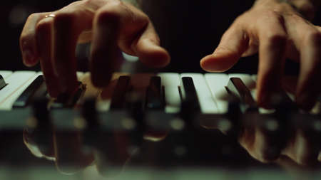 Closeup man hands pressing keys on synthesizer in dark hall. Unrecognizable person making music in recording studio. Unknown male musician playing piano keyboard indoor. Banco de Imagens - 158235828