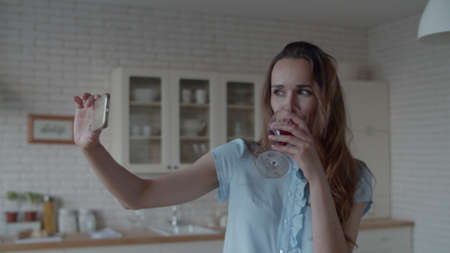 Close up young woman posing for photo with glass of red wine in kitchen interior in slow motion. Happy woman drinking wine in front of phone camera in kitchen. Pretty girl making video on smartphone.