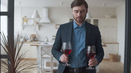 Attractive family couple drinking red wine at home together. Smiling man bringing glasses with wine to woman. Happy family celebrating success with alcohol drink on couch in slow motion.