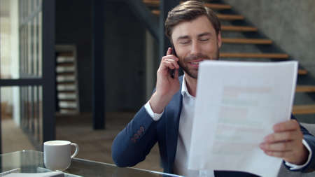 Portrait of happy businessman talking phone in office in slow motion. Joyful business man looking diagrams in remote office. Smiling top manager discussing documents on cellphone. Banco de Imagens - 158236215