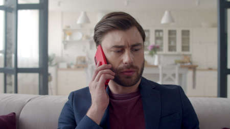 Closeup focused businessman having discussion on mobile phone in slow motion. Portrait of young guy feeling doubt at remote workplace. Feelancer man talking phone at home office. Banco de Imagens - 158236217