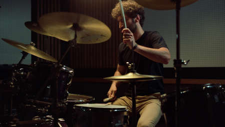 Bearded drummer performing solo on drum kit in recording studio. Rock musician playing rock music in concert hall. Emotional curly hair artist hitting drum cymbals with drumsticks in slow motion. Stockfoto