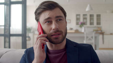 Closeup surprised business man talking mobile phone at remote workplace. Portrait of wondered guy having phone call at home office. Freelancer man saying no in slow motion. Banco de Imagens - 158236345