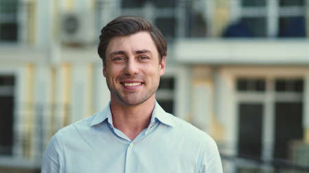 Portrait of happy business man smiling on camera at street. Cheerful businessman looking at camera outdoor. Close up joyful man standing in shirt at street.