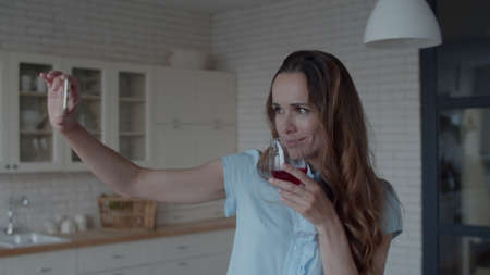 Young woman taking selfie photo on phone in kitchen interior. Portrait of happy girl posing with wine glass to phone camera in kitchen. Joyful woman winking to camera with glass of red wine at home Banco de Imagens