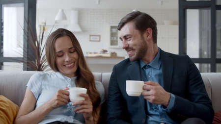 Portrait of happy family couple drinking tea at home. Husband and wife making coffee break after work. Successful couple talking on sofa in living room in slow motion.