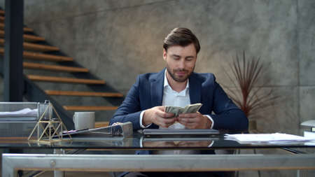Successful business man counting money at workplace. Portrait of joyful businessman throwing money away in slow motion. Smiling man enjoy good deal at modern office. Man made easy money. Banco de Imagens
