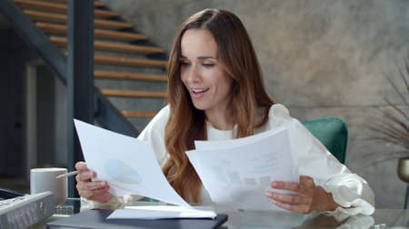 Closeup joyful business lady analyzing financial report at remote workplace. Attractive girl feeling excited in office. Happy business woman reading documents at office desk in slow motion.