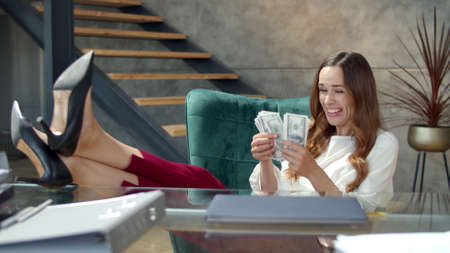 Closeup joyful business lady counting money in office in slow motion. Successful businesswoman celebrating good deal at office desk. Happy jackpot winner putting legs on desk at workplace.
